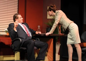 Edward Kassar and Elizabeth Donnelly confront each other at the desk